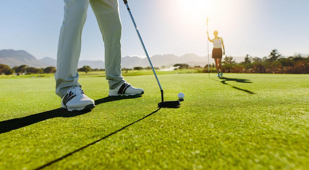 Golfer spielt Ball mit Partnerin im Hintergrund